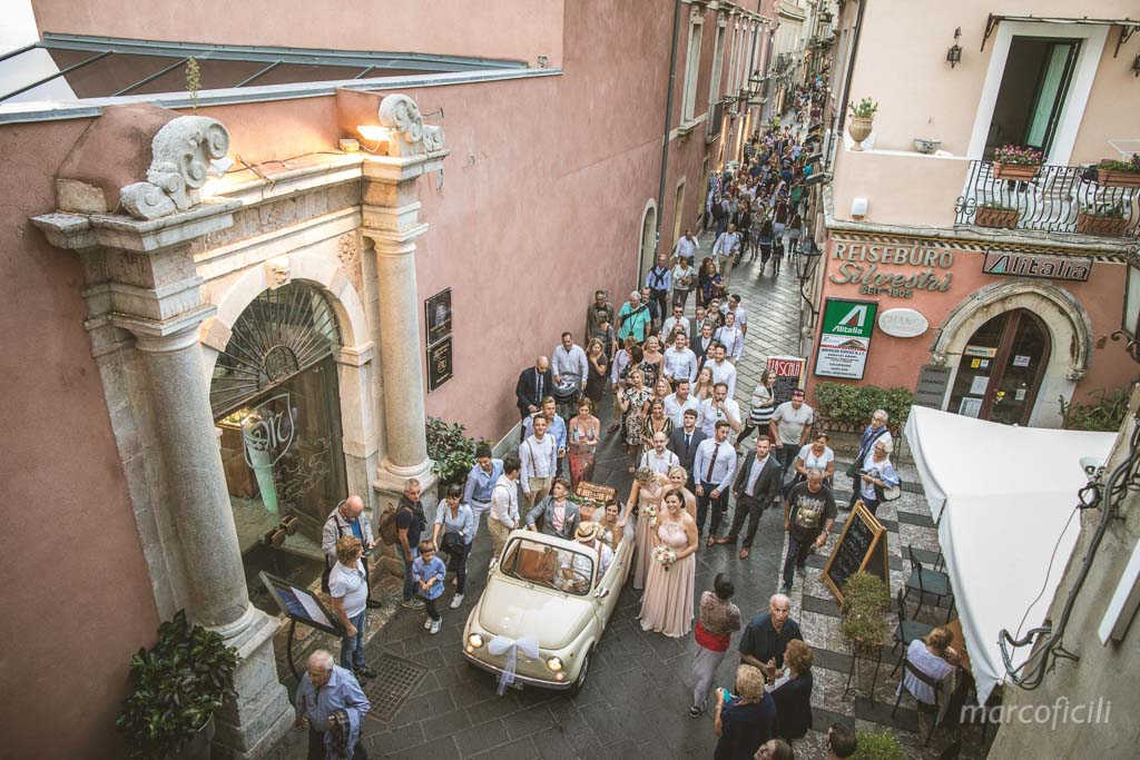 English Wedding Taormina _groom_bride_kiss_500_car_vintage_corso_umberto_taormina_view